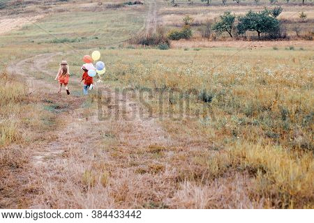 Cute Child With Balloons. Little Girl And Boy On A Walk. Enjoy Moment. Happy Child In Summer In Natu