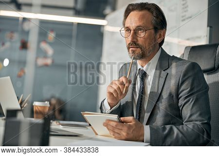 Director Of Department Wearing Glasses Sitting At The Office Table