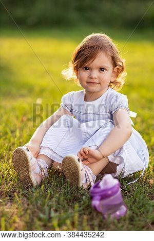 Cute, Little Two Year Old Girl In White Dress Sits In The Grass
