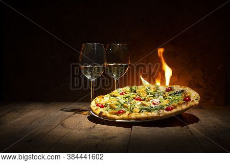 A Tasty Pizza Just From The Stove And Two Wine Glasses Standing On The Wooden Rustic Table Against T