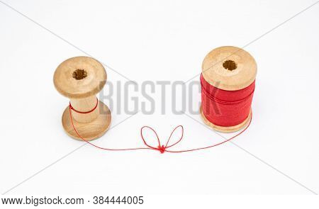 Two Wooden Spools Of Thread. One Is Full, The Other Almost Empty, Connected By A Single Thread With