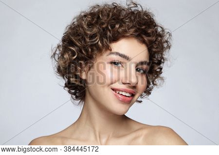 Portrait of smiling beautiful girl with curly hair and natural makeup
