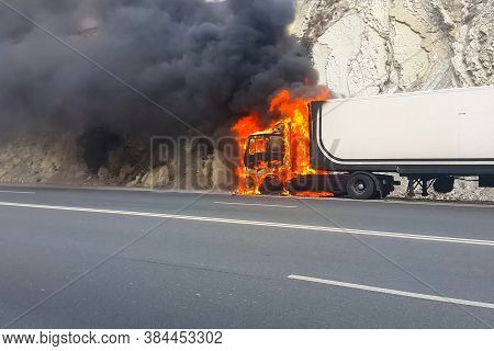 Burning Truck On The Road. The Cab Of The Truck Is On Fire.