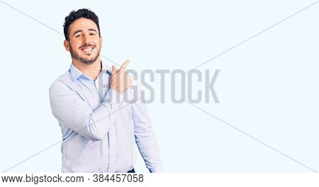 Young hispanic man wearing business clothes cheerful with a smile of face pointing with hand and finger up to the side with happy and natural expression on face