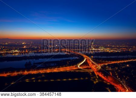 Aerial View Of Night Vienna . Illuminated Cityscape And Danube River In Wien