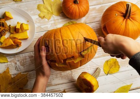 Halloween carving. Close up of kid hands with pumpkin or jack-o-lantern and knife at home. Decoration and holidays concept