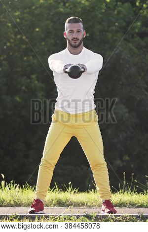 Front View Of The Sporty Young Guy Is Exercising With Kettlebell Sport Equipment Outdoors.