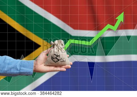 The Concept Of Economic Growth In Republic Of South Africa. Hand Holds A Bag With Money And An Upwar