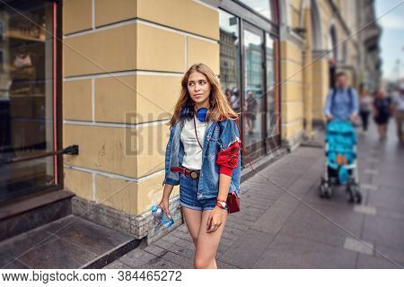 Beautiful Woman Is Walking Down Crowded Street. Young Caucasian Female 25 Years Old In Shorts Walks