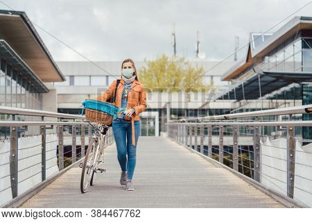 Woman with face mask pushing her bike over a bridge during coronavirus crisis