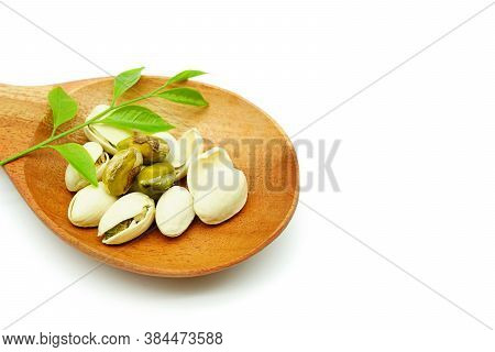 Pistachios In A Wooden Spoon Isolated On A White Background. Roasted Pistachio Seeds In Shells And S