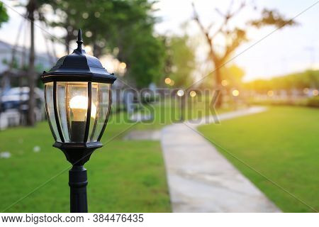 Close Up Europe Style Pole Of Lamp With Light On In Green Grass Field At Evening.