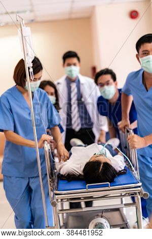 Seriously injured patient with oxygen mask on gurney stretcher bed pushed by medical team of doctor nurse and paramedic to the Operating Room. Emergency health care and medical hospital concept.
