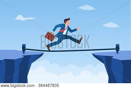 Businessman Is Walking A Tightrope Across The Gap Between The Rocks. Business Concept Risk And Dange