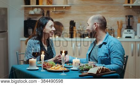 Young Man Making Proposal To His Girlfriend During Romantic Dinner, In The Kitchen, Sitting At The T