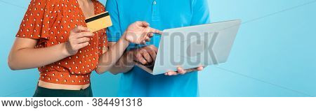 Partial View Of Woman In Red Blouse Holding Credit Card And Pointing With Finger At Laptop In Hands