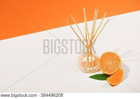 Air Freshener With Reed Sticks On A White Plate With Orange Tangerine. Room Aromatization With A Dif