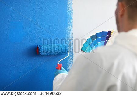 Craftsman Holds Roller And A Color Palette And Paints White Wall Blue. Wall Painting Services And Pa
