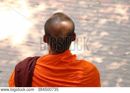 Head And Beside Of Asian Monks Or Buddhist Monks Which Wears A Dress In Yellow Or Orange.