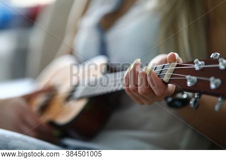 Close-up Of Adult Person Holding Acoustic Guitar And Playing Melody. Female Hand Placed On String. S