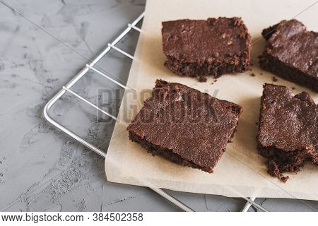 Pieces Of Homemade Chocolate Brownie Cake Served On A Metal Tray With Baking Paper