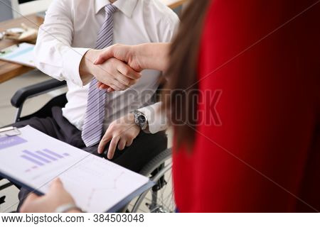 In Office, Man In Wheelchair Greets A Colleague With A Handshake. Equal Rights For People With Disab