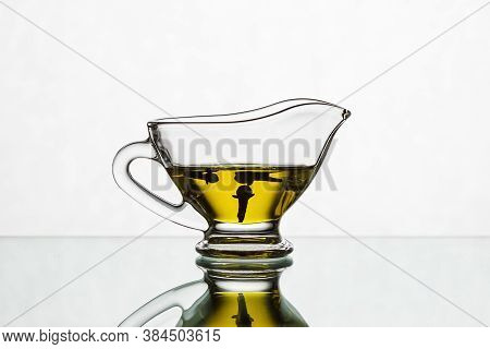 Clove Oil In A Glass Sauceboat On A White Background. Cloves In A Gravy Boat