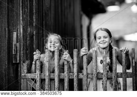 Two little cute girlfriends look out for wooden village fence. Black and white photo.
