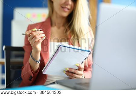 Woman Sits At Workplace With Notebook Pen In Her Hands. Online Vocational Training Concept