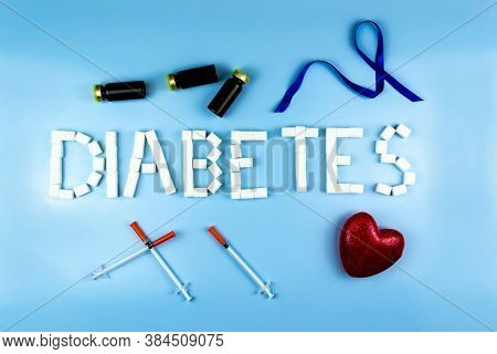 Lined With Cubes Of Sugar Diabetes , Next To Insulin Syringes, A Heart, Bottles Of Insulin And A Blu