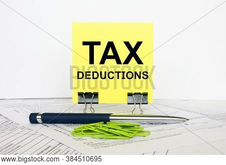 Yellow Sticker With Text Tax Deductions Stands On Office Clips. Next To It Is A Blue Pen With Green