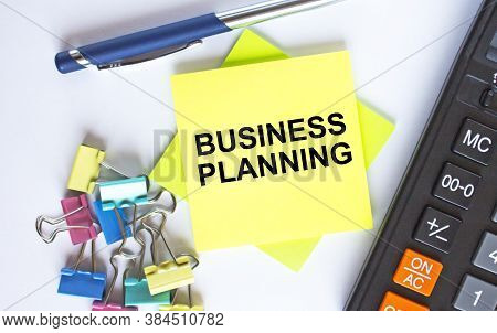 Text Keep Business Planning On Yellow Stickers With Calculator, Blue Pen And Paper Clips