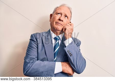 Senior handsome grey-haired businessman wearing elegant suit over white background thinking concentrated about doubt with finger on chin and looking up wondering