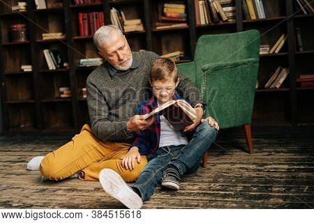 Senior Grandfather And Little Grandson Reading Interesting Book Together Sitting On Floor On Home Li