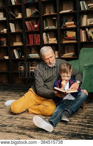 Happy Old Senior Grandfather And Little Grandson Reading Interesting Book Together Sitting On Floor