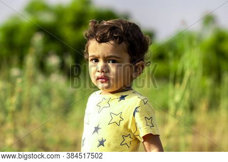 A Sad Little Indian Child Angrily Looking At The Camera, Asian Kids In Nature, Portrait Little Boy O