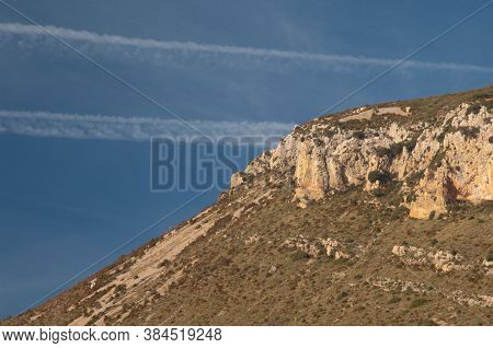 Contrails Of Airplanes And Cliff In The Guara Mountains.