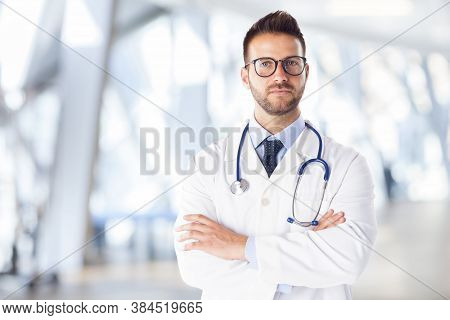 Male Doctor Portrait Looking At Camera And Smiling While Standing In The Hospital