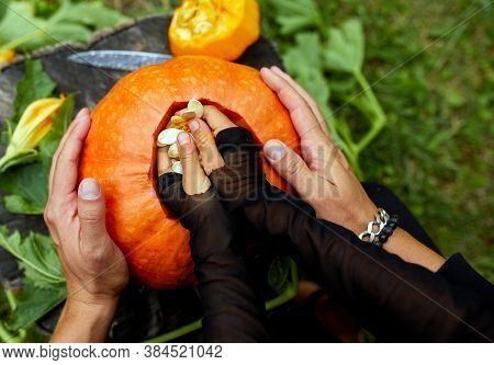 Daughter And Father Hands Carving Pumpkin For Halloween, Prepares Jack Olantern