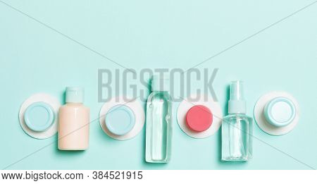 Set Of Travel Size Cosmetic Bottles On Blue Background. Flat Lay Of Cream Jars. Top View Of Bodycare