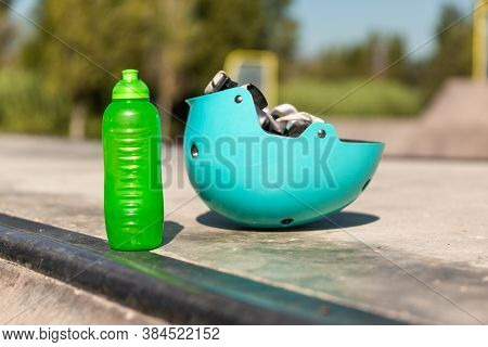 A Protective Blue Cyan Skater Helmet And A Transparent Green Water Bottle In A Skate Park