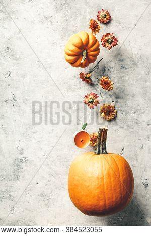 Levitating Orange Pumpkin And Chrysanthemum Against Old Background