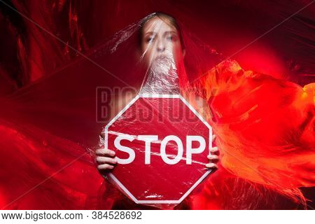 Portrait Of Girl, Can No Breathe, Holding Sign Stop. Young Woman Is Choking, Wrapped In Plastic Bags