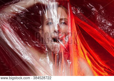 Portrait Of Dying Unhappy Girl, Can No Breathe. Young Woman Is Choking, Wrapped In Plastic Bags, Pol