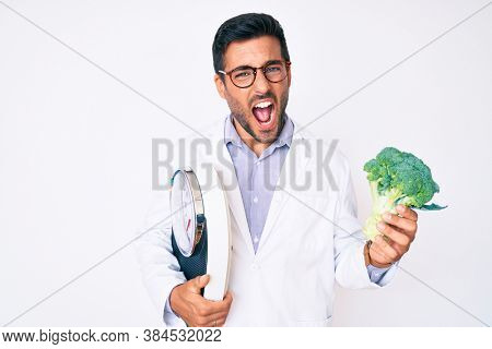 Young hispanic man as nutritionist doctor holding weighing machine and broccoli angry and mad screaming frustrated and furious, shouting with anger. rage and aggressive concept.