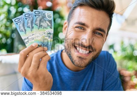Young hispanic man smiling happy holding australian dollars banknotes at the terrace.