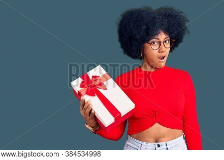 Young african american holding gift in shock face, looking skeptical and sarcastic, surprised with open mouth