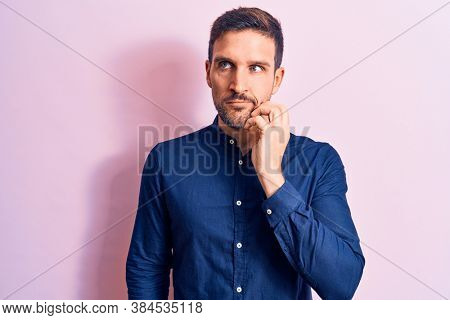 Young handsome man wearing casual shirt standing over isolated pink background thinking concentrated about doubt with finger on chin and looking up wondering