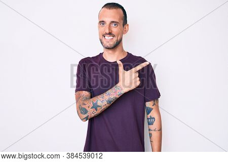 Young handsome man with tattoo wearing casual clothes cheerful with a smile of face pointing with hand and finger up to the side with happy and natural expression on face