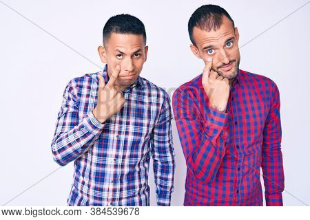 Young gay couple of two men wearing casual clothes pointing to the eye watching you gesture, suspicious expression